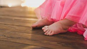 Child's Feet on Hardwood Flooring