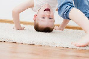 Laughing kid is standing upside down on white carpet on rug